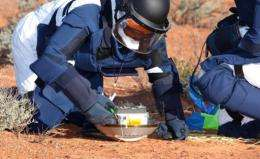A team of scientists inspect the capsule carried by the Japanese Hayabusa spacecraft after it landed in Australia