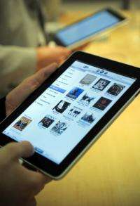 Customers try out Apple's new iPad in a shop in Barcelona