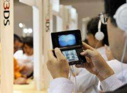 """Visitors examine Nintendo's portable videogame console with a 3D display called the """"Nintendo 3DS"""""""