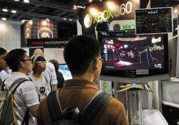 Visitors play the Xbox 360 video games at the Games Convention Asia exhibition in Singapore
