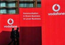 Visitors walk past Vodafone exhibition stand walls