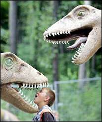 A German youth sticks his head in the mouth of a dinosaur figure