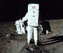 Buzz Aldrin totes experiments from the Eagle onto the lunar surface.