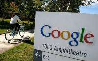 A Google employee rides a bicycle by a sign at the company's headquarters