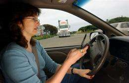 A woman dials a cell phone in her car