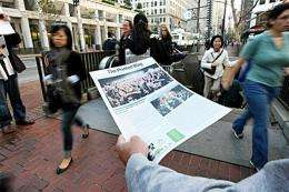 """A man hands out free copies of """"The Printed Blog"""" in San Francisco"""
