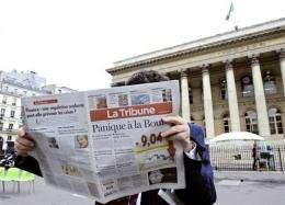 A man reads French economical newspaper La Tribune in front of the Palais Brongniart