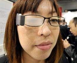 "A Masunaga Optical employee displays the blinking ""Wink Glasses"""