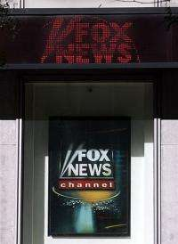 An electronic news ticker above a sign at the Fox News Channel television studios in New York.