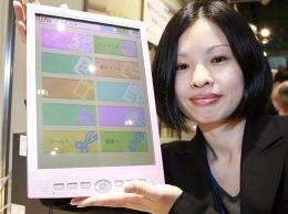 """An employee of Japanese computer giant Fujitsu displays the company's mobile information terminal """"FLEPia"""""""
