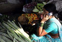 An Indian vendor uses her mobile phone to take customers orders
