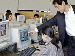 An teacher instructs a student in a Tokyo computer lab