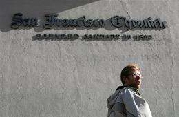 A pedestrian walks by the San Francisco Chronicle building in February 2009 in San Francisco, California.