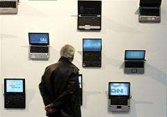 A visitor looks at laptops at a computer fair