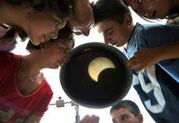Bulgarian children look at a eclipse of the sun through a telescope in the Black Sea port of Varna