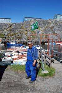 Greenlandic fisherman Johannes Heilmann poses for a photo in front of the shipping harbor of Nuuk fjord