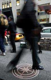 New York residents walk on the sidewalk  in Manahattan in New York