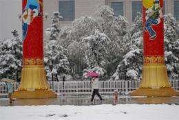 Pedestrians make their way across the snow in Tian'anmen Square