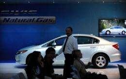 A man walks past a 2012 Honda Civic Natural Gas vehicle