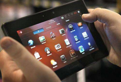 An employee demonstrates a Blackberry Playbook tablet