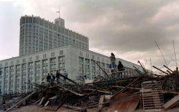 People stand on the barricades surrounding the Russian White House in Moscow on August 24, 1991