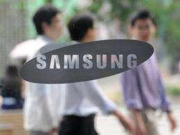 South Korean men walk past a Samsung logo in Seoul