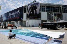 Workers hang banners in preparation for the E3 Expo
