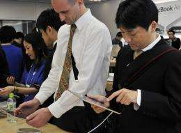 Customers check a tablet PC in a store in Tokyo