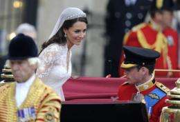 Prince William (R) and his wife Kate, Duchess of Cambridge climb into a carriage after their wedding service in London