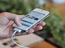 A customer looks at an Apple iPhone 4S