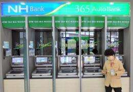 A bank customer is seen in front of a series of ATMs in Seoul