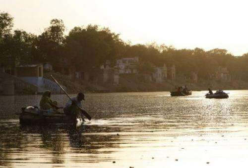 A couple collect refuse floating on the Yamuna River in New Delhi in June