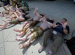 """Adam Ghiggio from Australia poses next to mutant mannequins wich are lined up to be used as displays for """"Rage"""""""