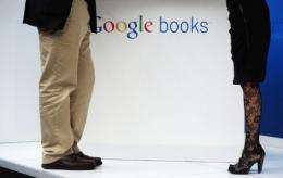 "A man and a woman stand at a Google stand, next to a ""Google books"" logo"