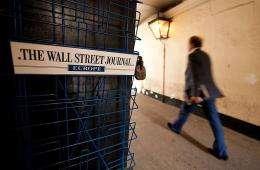 "A man passes an empty newspaper rack displaying a ""Wall Street Journal"" sticker in London"