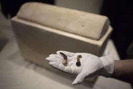 A man shows two Roman nails next to a Roman period ossuary