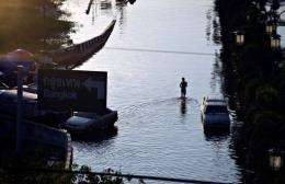 A man wades the flooded neighbourhood of Rangsit district on the outskirts of Bangkok