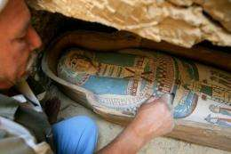 An Egyptian worker brushes the dust off a coffin containing mummy found at Lahun, southwest of Cairo,