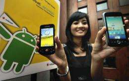 A woman at at launch in Jakarta last year displays smartphones using Google's Android operating system