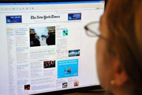 A woman reads the front page of the New York Times on the Internet, in Washington, DC