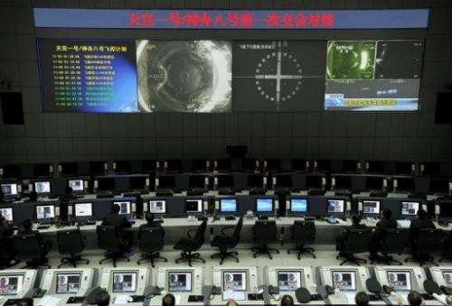 Chinese scientists monitor the docking of the Tiangong-1 space lab module and the Shenzhou VIII spacecraft