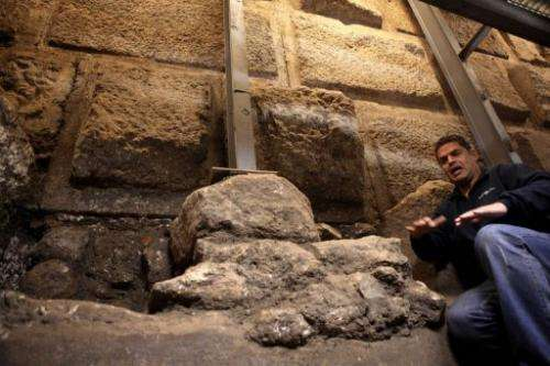 Eli Shukron of the Israel Antiquities Authority kneels inside a ritual bath exposed beneath the Western Wall