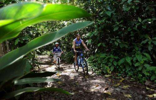 Joseph Mercadillio cycles with his son Jose Isaiah Mercadillio in a forest reserve in Manila on Environment Day