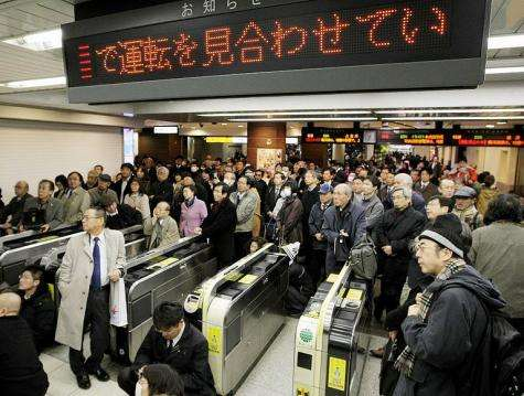People wait for transport services to resume at the Tokyo station