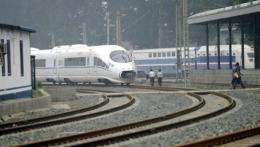 People walk next to a high-speed train at the railway test complex in Beijing