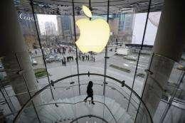 A customer walks under an Apple logo sign in in Shanghai in February 22