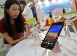 """A South Korean woman inspects Samsung's smartphone """"Galaxy Note"""" during an IT show in Seoul"""
