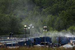 Men work on a natural gas valve at a hydraulic fracturing site