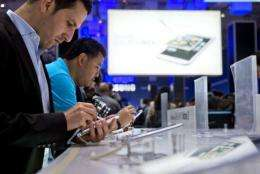 Visitors try out the smaller tablet Galaxy Note II