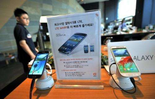 A man walks past Samsung smart phones at a mobile phone shop in Seoul on August 27, 2012